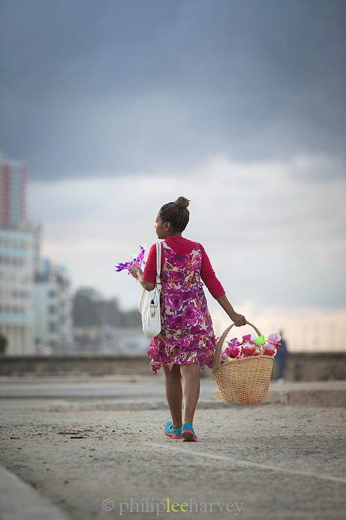 Woman selling flowers walking on road, Havana, Cuba