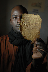 Boubacar Sadeck, the last caligrapher in Timbuktu, Mali holds ancient manuscripts that his family owns in his home March 6, 2007. In the past few years, with funding from different organizations including the Ford Foundation, thousands of the manscripts are being recovered, stored, preserved and studied. Sadly, many of them have been lost or severley damaged but for those that remain it is a maginifcent reminder of Africa's literary history.  (Photo by Ami Vitale),