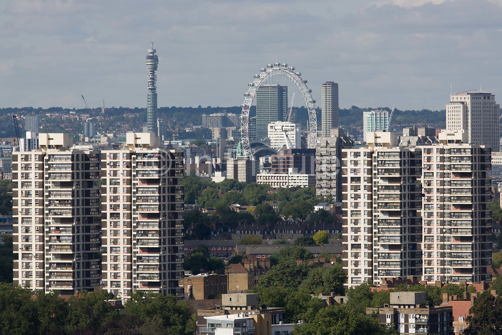 An aerial view of south London looking across the southern boroughsfrom Camberwell towards Lambeth tower blocks and the London Eye on Southbank. The skyline of this modern metropolis is seen on a bright autumnal day before the capital's leaves drop from trees. Four tower blocks stand at either side of this landscape and Westminster is seen in the middle, where London's most-visited attraction - the Eye - revolves slowly for visitrs to see in all directions.