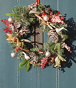 Christmas wreath decoration hanging on front door of house, UK