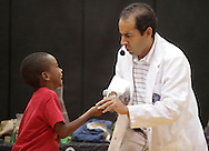Middletown, New York - Erik Maldonado, right, reacts after a spoon held by a young boy made funny noise when held against a block of dry ice during a Mad Science demonstration at the YMCA summer camp on August 20, 2010.