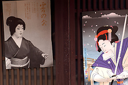 Posters on wall of old wooden building showing traditional female designs in Gion Kyoto