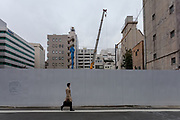 A Japanese salaryman walks past a site being redeveloped in Kanda, Tokyo, Japan. Monday April 1st 2019