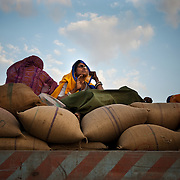 A women catching a ride on a back of a loaded truck on the Delhi-Jaipur highway bids farewell to the setting sun.