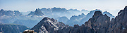 """From Rifugio Guido Lorenzi on Monte Cristallo in the Ampezzo Dolomites, look northeast across blue ridges of the Sesto Dolomites (Dolomiti di Sesto, or Sexten/Sextner/Sextener Dolomiten) to the pyramids of Tre Cime di Lavaredo (Italian for """"Three Peaks of Lavaredo,"""" called Drei Zinnen or """"Three Merlons"""" in German). A lift to Forcella Staunies on Monte Cristallo gives unforgettable views over the Dolomites mountains (part of the Southern Limestone Alps) near Cortina d'Ampezzo, in the Province of Belluno, Veneto region, Italy, Europe. Monte Cristallo lies within Parco Naturale delle Dolomiti d'Ampezzo. Directions: From Cortina, drive 6km east on SR48 to the large parking lot for Ski Area Faloria Cristallo Mietres (just west of Passo Tre Croci Federavecchia). Take a chair-lift from Rio Gere to Son Forca (rising from 1698m to 2215m). Then take the old style ovovia (egg-shaped) Gondellift Forcella Staunies to Rifugio Guido Lorenzi (2932m) for astounding views. Climbers enjoy spectacular via ferrata routes here. Cortina gained worldwide fame after hosting the 1956 Winter Olympics. UNESCO honored the Dolomites as a natural World Heritage Site in 2009. This panorama was stitched from 4 overlapping photos."""
