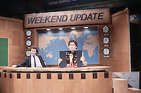 ca. 1986 --- Dennis Miller and Al Franken perform a Weekend Update skit on NBC's Saturday Night Live. Al shows a photograph of his son, Joe, who is naked and holding a football. The idea is that because Joe is not skinny, people laugh, and Al can deduct food expenses for the IRS. --- Image by © Owen Franken/Corbis