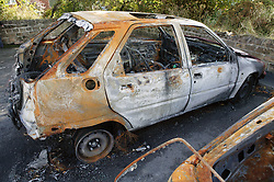 Remains of a burnt out car in a car park,