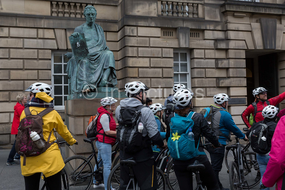 Cycling tourists listen to their guide beneath the statue of philosopher David Hume 1711 -1776, in Edinburgh, on 25th June 2019, in Edinburgh, Scotland. Completed in 1995 by sculptor Sandy Stoddart, it is situated in front of the High Court Building formally the Sheriff Court on the Royal Mile.