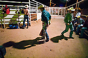23 AUGUST 2002 -- PHOENIX, AZ: Tonka Baj, from Waddell, AZ, prepares his bullriding gear before competing in Friday night bullriding at Mr. Lucky's, a county bar in Phoenix. The bar used to have bullriding in a small corral behind the bar.  PHOTO BY JACK KURTZ