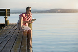 Mature man using digital tablet on pier and looking over lake, Bavaria, Germany