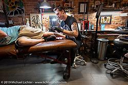 Bobby Ellis tattooing at his Victory Tattoo shop on Main Street during Daytona Beach Bike Week, FL. USA. Saturday, March 16, 2019. Photography ©2019 Michael Lichter.