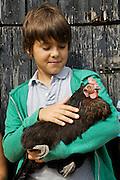 "Edward, 12, holding ""Bat"" the chicken in the chicken run at Hares Farm. CREDIT: Vanessa Berberian for The Wall Street Journal<br /> UKFARM-Hares Farm"