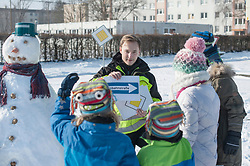 Man teaching road safety to children using arrow sign