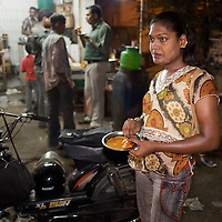 Kavia, an Aravani takes a break for food while looking for sex works on the streets of  Chennai...India's transexual community has a recorded history of more than four thousand years. Many consider the The Third Sex, also known as Aravanis, to posses special powers allowing them to determine the fate of others. As such, they are not only revered but despised and feared too. Resigned to the fringes of society, segregated and excluded from most occupations, many Aravanis are forced to turn to begging and sex work in order to earn a living. ..The annual transgender festival in the village of Koovagam, near Vilappuram, offers an escape from this often desolate existence. For some, the week-long partying and frenetic sex trade that culminates in the Koovagam festival is about fulfilling lustful desires. For others, the gathering provides a chance for transgenders to bond, share experiences, join the wider homosexual gay-community and coordinate their campaign for recognition and tackle the challenge of HIV/AIDS. ..It is the Indian state of Tamil Nadu that the eighty-thousand-strong Aravani community has made advances in their fight for rights. In 2009, the Tamil Nadu state government began providing sex-change surgery free of cost. The state has also offers special third-gender ration cards, passports and reserved seats in colleges. And 2008 the launch of Ippudikku Rose, a Tamil talk-show fronted by India's first transgender TV-host and the release of a mainstream Tamil film staring an Aravani in the lead-role. ..These advances clearly signal a victory for south India's transgenders, but they have also exposed deep divisions within the community. There is a very real gulf that separates the majority poor from their potentially influential but often reticent, upper-class sisters. ..Photo: Tom Pietrasik.Chennai, Tamil Nadu. India.May 2009