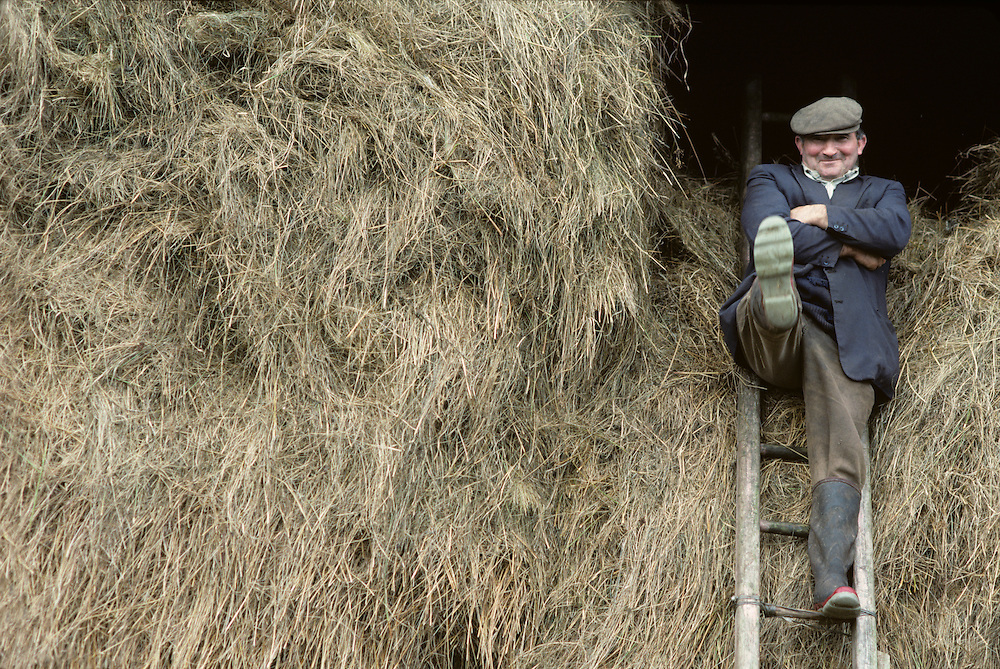Ireland, Inaugh, County Clare, Farmer Mickey Cullinan clowns atop hayloft of family barn in farming village
