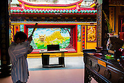 """12 APRIL 2012 - HO CHI MINH CITY, VIETNAM:  A man prays opposite a relief of a tiger in Chùa Quan Âm (Avalokiteshvara Pagoda), a Chinese style Buddhist pagoda in Cho Lon. Founded in the 19th century, it is dedicated to the bodhisattva Quan Âm. The pagoda is very popular among both Vietnamese and Chinese Buddhists. Cholon is the Chinese-influenced section of Ho Chi Minh City (former Saigon). It is the largest """"Chinatown"""" in Vietnam. Cholon consists of the western half of District 5 as well as several adjoining neighborhoods in District 6. The Vietnamese name Cholon literally means """"big"""" (lon) """"market"""" (cho). Incorporated in 1879 as a city 11km from central Saigon. By the 1930s, it had expanded to the city limit of Saigon. On April 27, 1931, French colonial authorities merged the two cities to form Saigon-Cholon. In 1956, """"Cholon"""" was dropped from the name and the city became known as Saigon. During the Vietnam War (called the American War by the Vietnamese), soldiers and deserters from the United States Army maintained a thriving black market in Cholon, trading in various American and especially U.S Army-issue items.         PHOTO BY JACK KURTZ"""