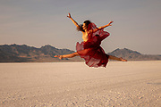 Woman in a maroon skirt leaping at the Bonneville Salt Flats with mountains in the background