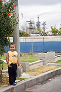 Young latino boy plays in the shadow of an oil refinery in Wilmington.