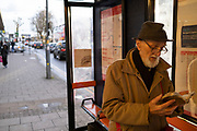 Elderly gentleman reading his book at a bus stop while out and about on Kings Heath High Street on 13th March 2020 in Birmingham, United Kingdom. Kings Heath is a suburb of Birmingham, three miles south of the city centre. It is the next suburb south from Moseley.