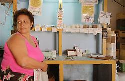 Female shopkeeper selling basic provisions in shop in Havana; Cuba,