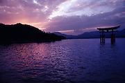 The sun is almost finished setting over a body of water in Japan, turning the water pink and purple