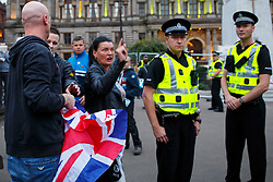 © Licensed to London News Pictures. 18/09/2014. Glasgow, UK. Police officers separating Unionists and Scottish Independence campaigners who met at George Square in Glasgow whilst people of Scotland going to polling stations to vote on the Scottish independence referendum on Thursday, 18 September 2014. Photo credit : Tolga Akmen/LNP
