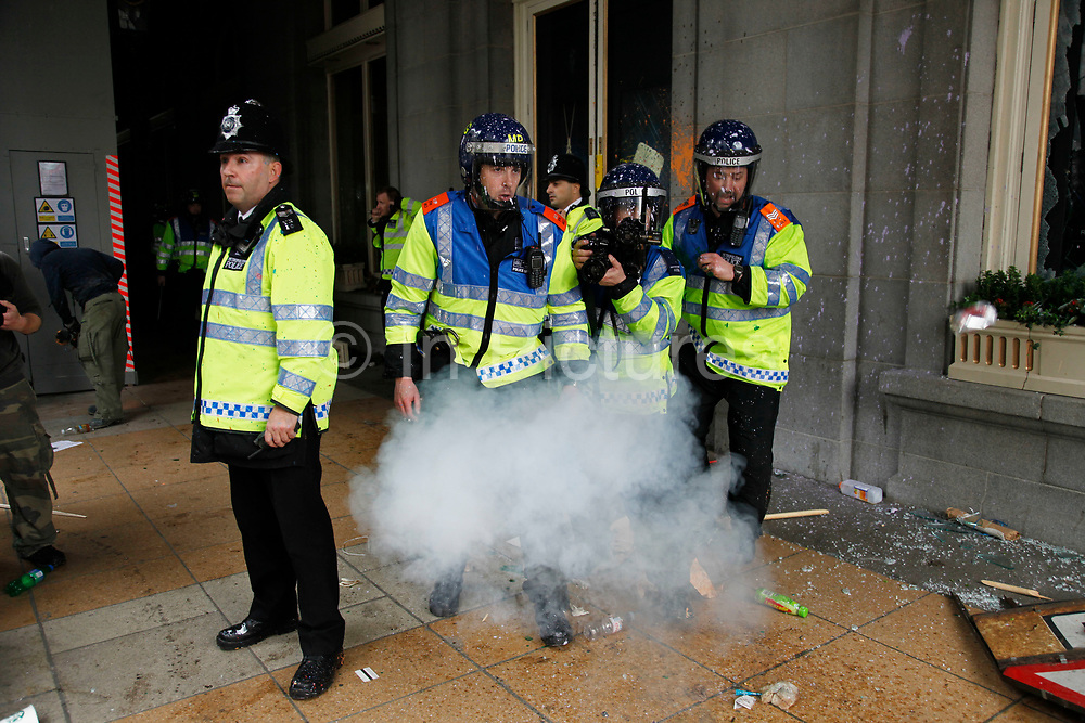 Riot police are pinned back by protesters throwing missiles at them as The Ritz  comes under attack. Anti capitalists / anarchists go on the rampage through central London on the back of the peaceful TUC protest march. The masked demonstrators ran a twisting route through the capital confusing the police and creating a situation which was very difficult to manage. The protesters attacked banks, shops and hotels, and the police in riot gear fought  face to face with them as they were pelted with ammonia, paint and fireworks loaded with coins.