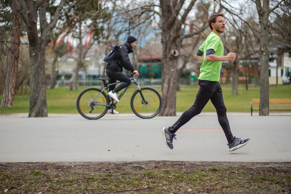 Cyclist and Jogger exercising in the park, Prater Park, Vienna, Austria