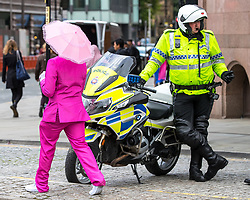 © Licensed to London News Pictures . 30/07/2017 . Manchester , UK . A man dressed in a pink suit and carrying a pink umbrella walks passed a motorcycle policeman who is watching over crowds at the venue . Cosplayers, families and guests at Comic Con at the Manchester Central Convention Centre . Photo credit : Joel Goodman/LNP
