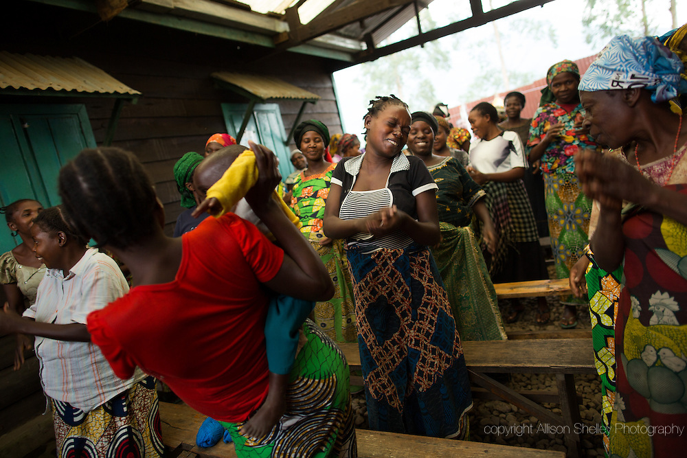"""Women dance at the """"Village de Accueil"""" at Masisi Hospital in North Kivu, Democratic Republic of Congo, July 28, 2014.  The village is the temporary home for 50 women who are in their final months of high risk pregnancy.  The home is a welcome option for many women in a region where conflict has shuttered many local clinics and made travel dangerous.  But women say that it is not an easy choice, as it often involves leaving other children at home under the supervision of other already burdened relatives."""