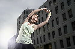 Mid adult woman stretching her body and listening to music, Bavaria, Germany