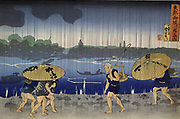 On the Bank of the Samida River in Mimayagashi', 1833.   Utagawa Kuniyoshi (1797-1861) Japanese Ukiyo-e artist. Men walking barefoot through heavy rain under umbrellas. Shadowy figures of boats on the river.  Weather Water Cloud