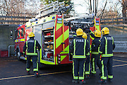 London Fire Brigade, station training session. Fire fighters get the ladders off the fire engine.