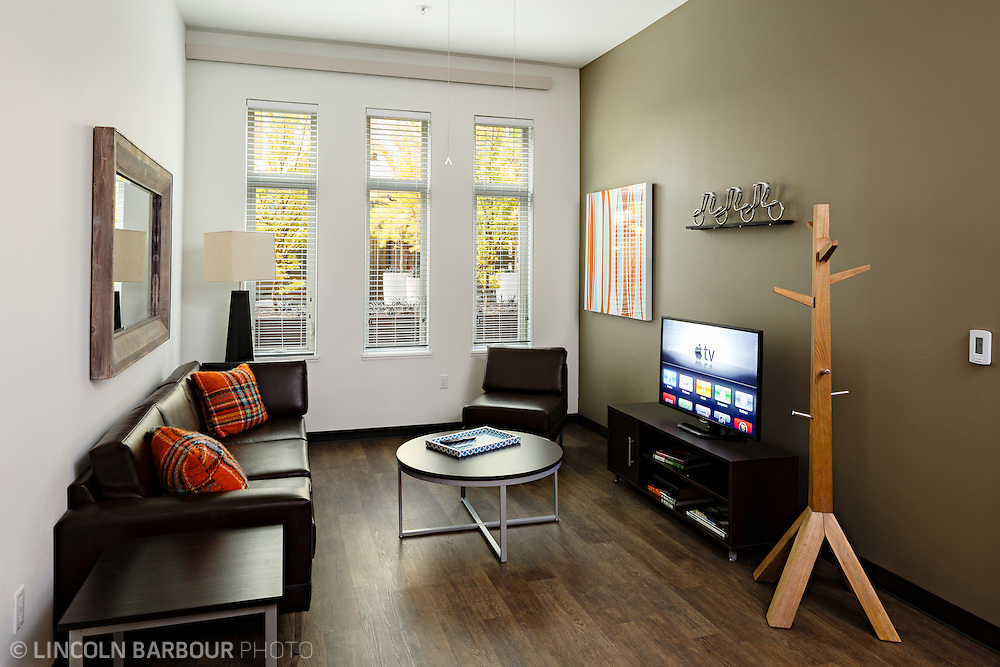 University House student housing apartment in Eugene, OR. Designed by Mahlum Architects. A small living room with a nice couch and cool coat rack.