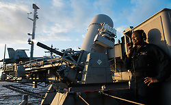 WATERS SOUTH OF JAPAN (Aug. 18, 2018) Fire Controlman 2nd Class Maris Cox, from New York, stands safety as a Phalanx close-in weapons system (CIWS) fires during a live-fire exercise aboard the Navy's forward-deployed aircraft carrier, USS Ronald Reagan (CVN 76). CIWS is a rapid-fire gun capable of firing 4,500 rounds per minute that provides defense against air contacts. Ronald Reagan, the flagship of Carrier Strike Group 5, provides a combat-ready force that protects and defends the collective maritime interests of its allies and partners in the Indo-Pacific region. (U.S. Navy photo by Mass Communication Specialist 2nd Class Kenneth Abbate/Released) 180818-N-OY799-0027