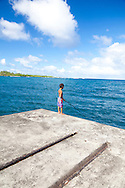Maui, Hawaii. A boy fishing off the end of the pier in Hana on a Sunday afternoon in Hana Bay, Maui. The railroad tracks leftover from the sugar plantation are visible.