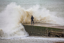 © Licensed to London News Pictures. 06/01/2018. Brighton, UK. A man just escapes being soaked by a large wave that hits the pontoon on the Brighton and Hove seafront. Photo credit: Hugo Michiels/LNP