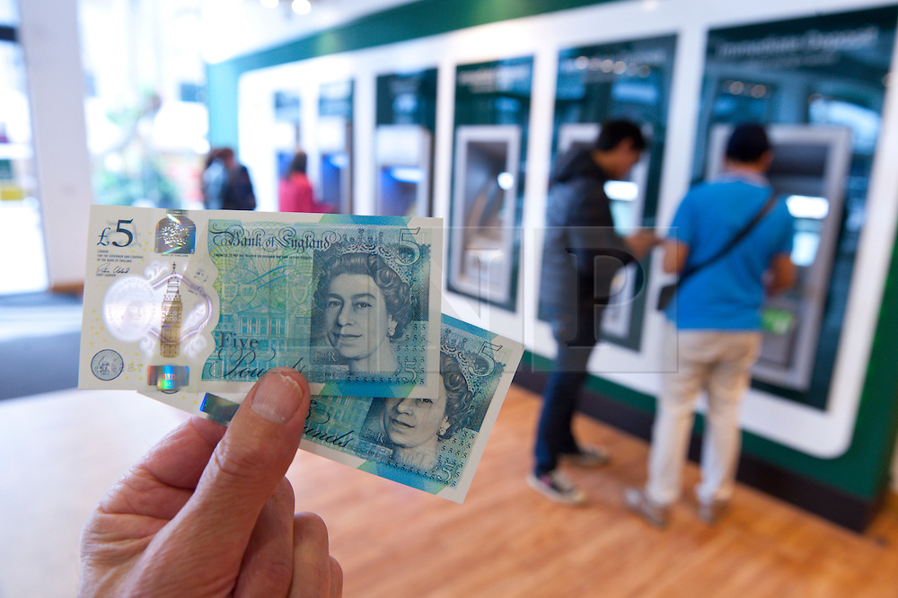 © Licensed to London News Pictures. 13/09/2016. Birmingham, West Midlands,  UK. New Five Pound Notes are withdrawn from the Lloyds Bank ATM at Corporation Street in Birmingham. This branch is one of the few issues the new notes. Photo credit: Graham M. Lawrence/LNP