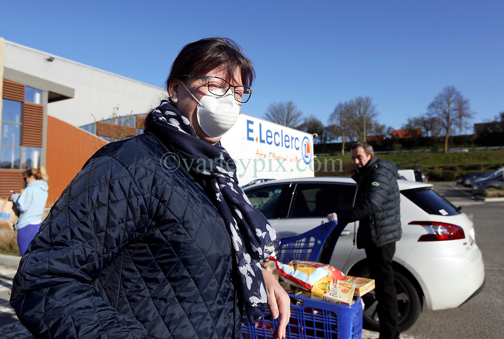 23 March 2020. Montreuil Sur Mer, Pas de Calais, France. <br /> Coronavirus - COVID-19 in Northern France.<br /> <br /> A woman wearing a face mask to help protect herself from coronavirus infection leaves Leclerc supermarket in Attin near Montreuil Sur Mer. Numbers entering the store at any one time are restricted to try and maintain 'social distancing,' in an effort to halt the spread of the virus. Anyone leaving their home must carry with them an 'attestation,' in a effect a self administered permit to allow them out of the house. If stopped by the police, one must produce a valid permit along with identification papers. Failure to do so is punishable with heavy fines. Movement in France has been heavily restricted by the government.<br /> <br /> Montreuil Sur Mer was the headquarters of the British Army under Field-Marshal Sir Douglas Haig from March 1916 to April 1919. Over 1,200 year old, the ancient fortified  town with its high ramparts has endured through history, surviving the plague and King Henry VIII's invasion of France in 1544 when the Duke of Norfolk under Henry VIII's command laid a disastrous siege to the town which held firm until Norfolk was forced to withdraw in 1545. Residents are confident the ancient town can survive the coronavirus too. <br /> Photo©; Charlie Varley/varleypix.com