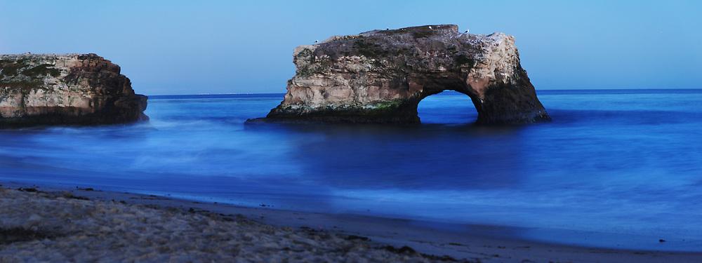 The arch is seen at dusk at natural bridges state beach in Santa Cruz, CA