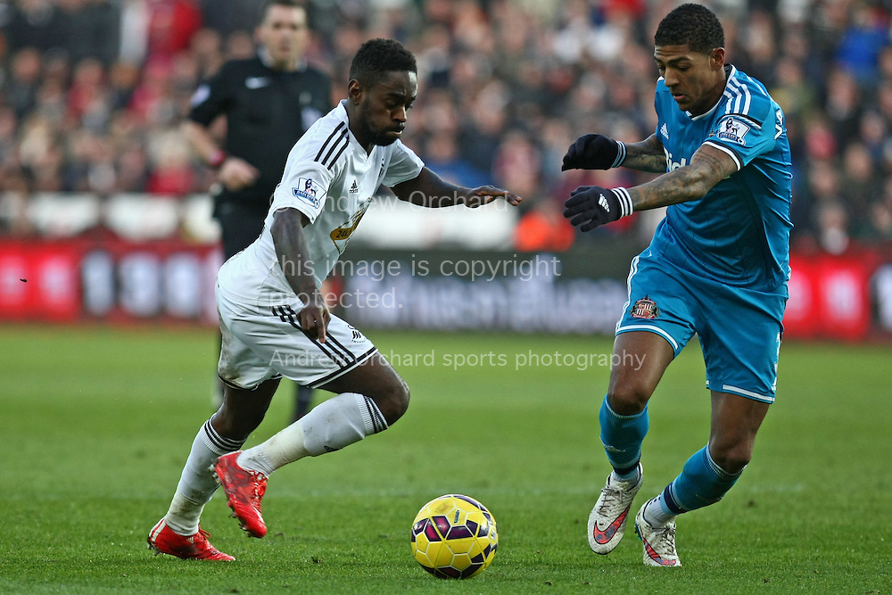 Nathan Dyer of Swansea (left) takes on Patrick van Aanholt of Sunderland.<br /> Barclays Premier League match, Swansea City v Sunderland at the Liberty stadium in Swansea, South Wales on Saturday 7th Feb 2015.<br /> pic by Mark Hawkins, Andrew Orchard sports photography.