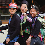 Black Hmong women and a baby on a motor bike in the main street of Sapa, Vietnam.  Sapa and the surrounding highlands are close to the Chinese border in Northern Vietnam and is inhabited by highland minorities including Hmong and Dzao groups. Sapa is now a thriving tourist destination for travelers taking the night train from Hanoi. Sapa, Vietnam. 16th March 2012. Photo Tim Clayton