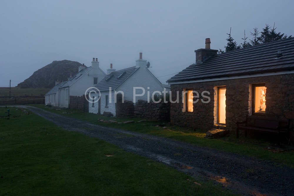Cottages in the remote bay at Kintra, Isle of Mull, Scotland. The lights are on in the nearest home and a puddle nearby reflects their warmth amid the otherwise bleak winter evening. Kintra is a small settlement on the north coast of the Ross of Mull. The name comes from the Gaelic for 'end of the beach', 'Ceann Tràgha'. It was founded by the 5th Duke of Argyll to provide an income for himself and his tenants through fishing. Originally cottages with thatched roofs did not have gable ends or chimneys but this one has one gable and with a chimney attached.