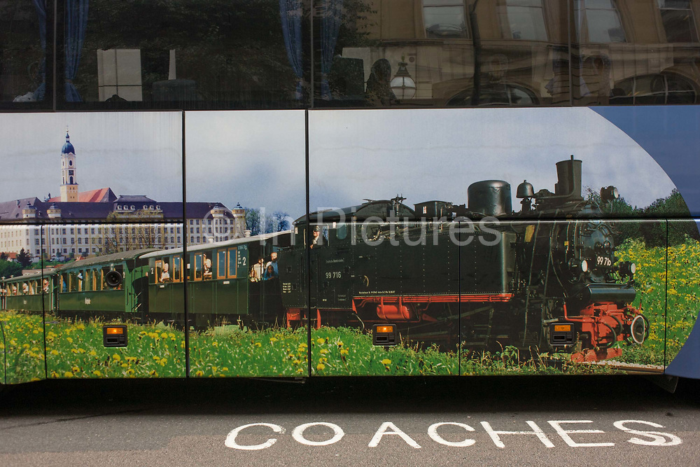 A tourist coach parked in central London shows an old steam train and carriages. The stencilled writing on the ground makes for a humerous landscape in the borough of Westminster. It is a scene about the golden age of steam travel - an era of smoke and soot when the locomotive ruled he country's rail network - and that of the modern era of road transportation. This tourist coach is parked near the famous buildings of Westminster Abbey and the Houses of Parliament, allowing visitors to disembark and leave again soon after their tour of the area.