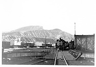D&RGW K-36 alongside Durango roundhouse.  An empty pipe train is in the background.<br /> D&RGW  Durango, CO