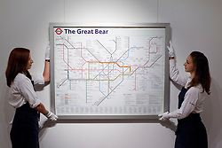 © Licensed to London News Pictures. 13/09/2013. London, UK. Two Sotheby's employees adjust Simon Patterson's 'The Great Bear' (1992) (est. GB£12,000-18,000), a lithograph based on the famous London underground tube map with station names changed using each line to represent groups of people, including scientists, saints, philosophers, comedians, explorers and footballers, at the press view for Sotheby's 'Prints and Multiples Sale' on New Bond Street in London today (13/09/2013). The auction, set to take place on the 17th of September, includes works by Munch, Rembrandt, Basquiat, Warhol and Picasso. Photo credit: Matt Cetti-Roberts/LNP