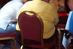 Very overweight person sitting on chair Yorkshire UK