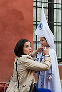 A mum checks everything is OK wit her little boy taking part in the Easter day, the last of all processions. Seville is the only city where a procession leaves on Easter day, la Resurrección (The Resurrection) founded in 1969 sale (gets out) in the street in white costume with a more joyful attitude. Seville, Spain
