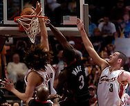 PHOTO BY DAVID RICHARD.Dwayne Wade, center, of Miami slam dunks against the defense of Cleveland's Anderson Varejao, left, and Sasha Pavlovic April 1, 2006 at Quicken Loans Arena.