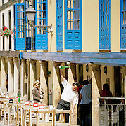 A waiter pouring water at a restaurant terrace in Oviedo, Asturias, Spain